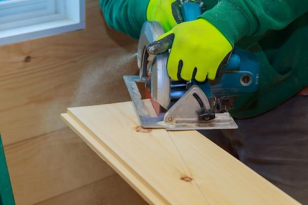 Detalhes de construção, trabalhador masculino, carpinteiro, usando serra circular para cortar tábuas de madeira, ferramentas elétricas