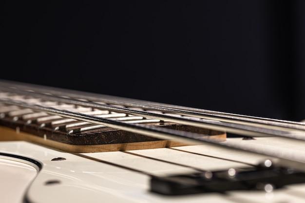 Detalhes de cordas de baixo da guitarra, close-up das cordas de ferro no espaço de cópia de fundo preto.