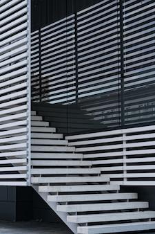 Detalhes de corrimão e escadas de um edifício moderno e reflexo de sombras nas janelas