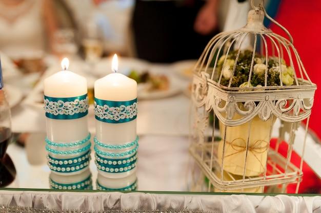 Detalhes de decoração de casamento. duas velas com ornamento azul perto da pequena gaiola decorativa branca vintage em uma mesa de vidro. fechar-se.