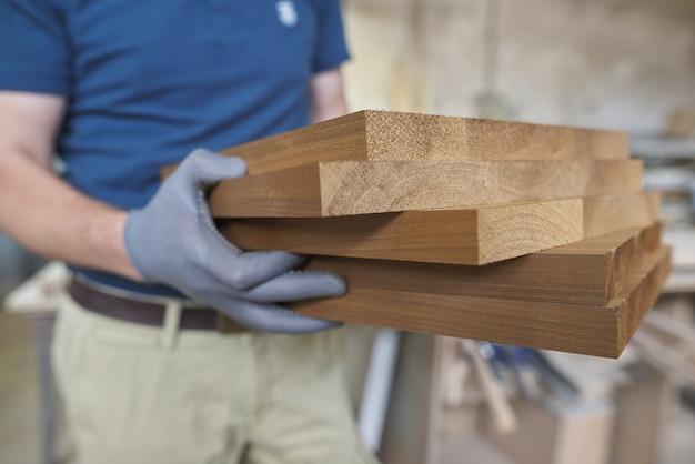 Detalhes de madeira nas mãos do carpinteiro masculino, indústria da madeira