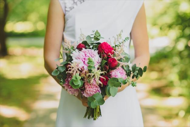 Detalhes de manhã nupcial. buquê de casamento nas mãos da noiva, foco selectoin