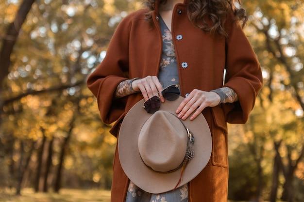 Detalhes de mãos de close-up de uma mulher atraente e elegante segurando um chapéu e óculos de sol andando no parque vestida com um casaco quente acessórios de estilo de moda de rua na moda outono