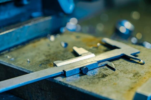 Detalhes de metal estão sobre a mesa perto do torno na fábrica.