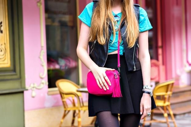 Detalhes de moda ao ar livre, roupa brilhante e moderna, minissaia, jaqueta de couro, bolsa colorida brilhante, posando perto do café francês, férias na europa.