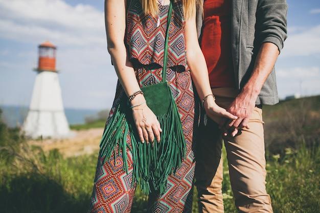 Detalhes de moda de mãos dadas com um casal jovem hippie em estilo indie apaixonado caminhando pelo campo, farol no fundo