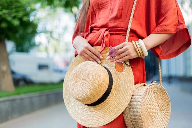 Detalhes de moda. mulher de vestido de verão coral elegante incrível posando na rua