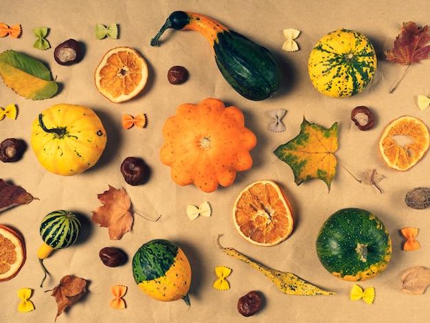 Detalhes de outono em papel artesanal abóboras castanhas laranjas secas folhas arcos de massa coloridos