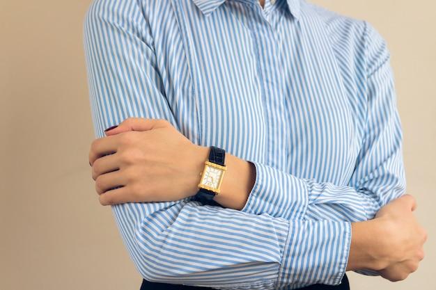 Detalhes de roupas. uma mulher em uma camisa azul com listras, na mão um relógio de ouro.