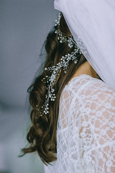Detalhes de um vestido de noiva. perto da garota sem rosto em lindo vestido de noiva branco. acessórios de noiva. espartilho, véu e renda. manhã da noiva.