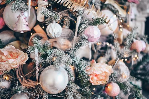 Detalhes de uma árvore de natal decorada em tons suaves de rosa.