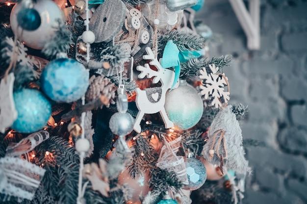 Detalhes de uma árvore de natal decorada nas cores turquesa e laranja escuras com veado de brinquedo branco