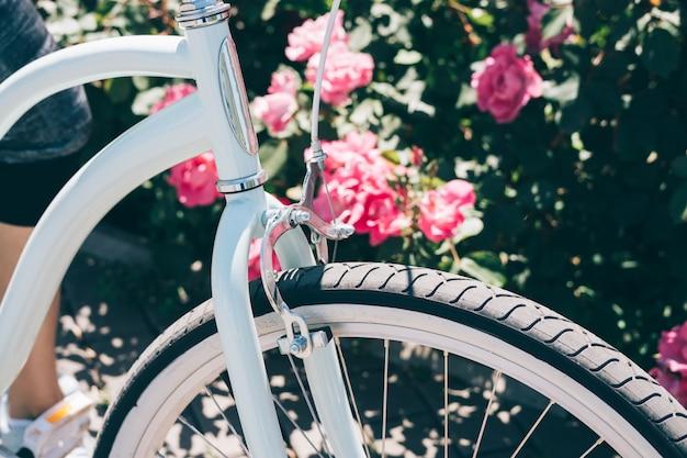 Detalhes de uma bicicleta à moda contra um fundo de arbustos com rosas em um dia ensolarado de verão