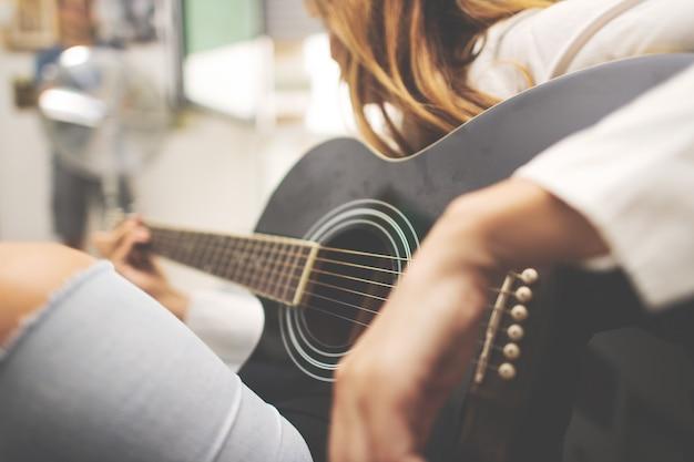 Detalhes de violão na mão de uma mulher canhota