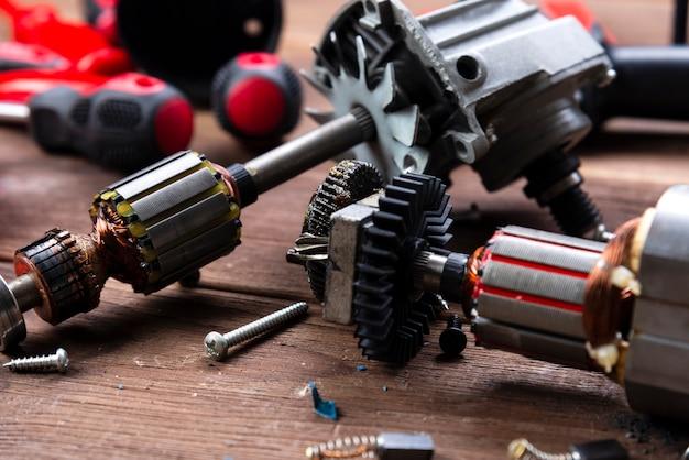 Detalhes do aparelho elétrico e ferramentas de reparo em uma mesa de madeira em uma oficina