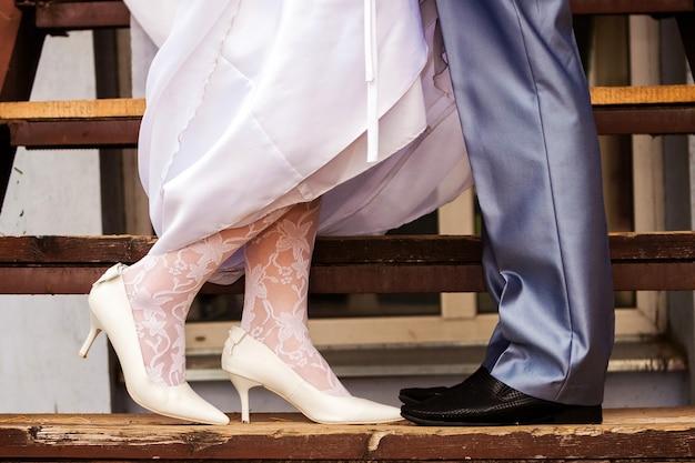 Detalhes do casamento: pernas da noiva em meia-calça de renda e do noivo nos degraus de madeira da escada