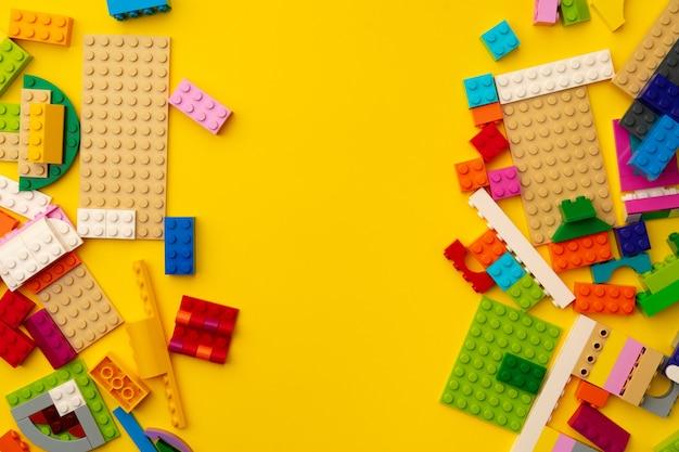 Detalhes do construtor de brinquedos infantis espalhados em amarelo