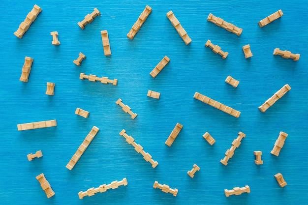 Detalhes do designer infantil de madeira sobre um fundo azul, quebra-cabeça de elementos de madeira. brinquedo para o desenvolvimento de habilidades motoras de pensamento e design.