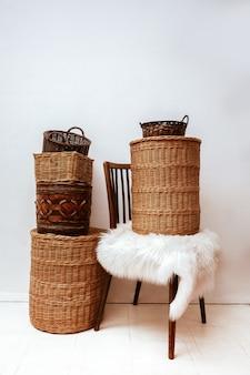 Detalhes do interior com cadeira de madeira natural e cestos de vime de salgueiro para armazenamento doméstico