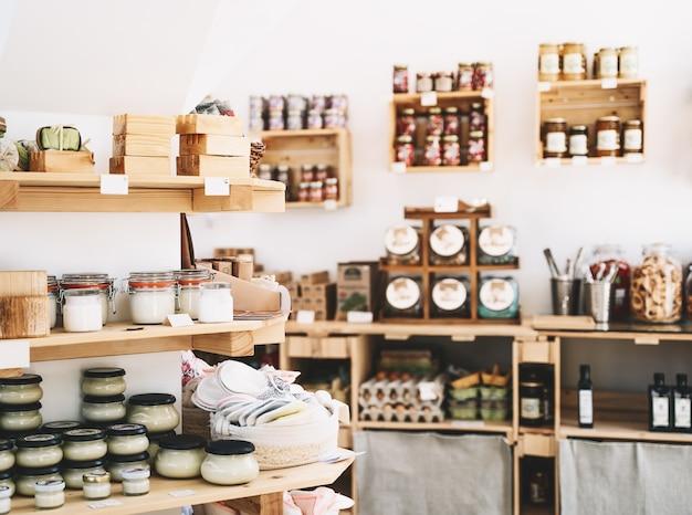 Detalhes do interior da loja com desperdício zero. prateleiras de madeira com diversos produtos alimentícios e de higiene pessoal ou cosméticos em mercearia sem plásticos. compras ecológicas em pequenas empresas locais