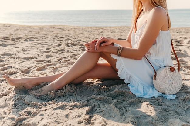 Detalhes fashion close-up de mulher em vestido branco com bolsa de palha no estilo verão em acessórios de praia