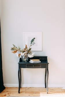 Detalhes luminosos do interior em estilo moderno. vaso e buquê de flores secas na mesa.