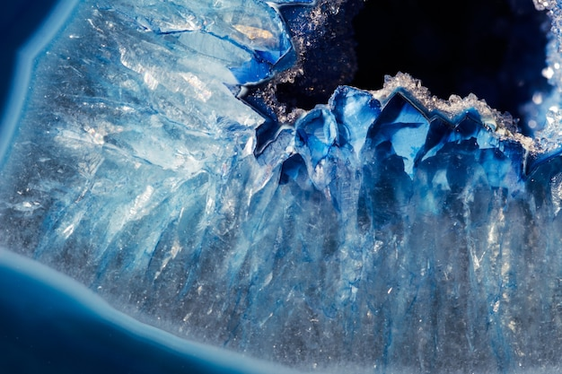 Detalhes macro de um mineral de ágata azul na superfície reflexiva. a ágata tem uma estrutura zoneada típica e é visível até a olho nu.