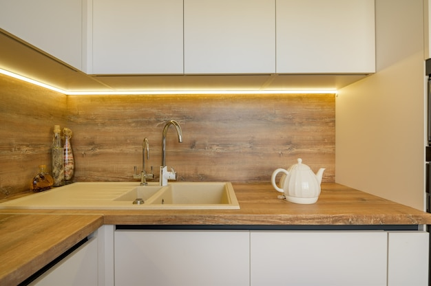 Detalhes modernos do interior da cozinha em madeira branca e bege