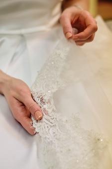 Detalhes tocantes da mão da noiva de seu vestido de casamento. manicure francesa simples