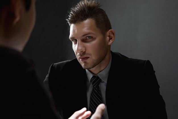 Detective entrevistando suspeito na sala de interrogatório escura