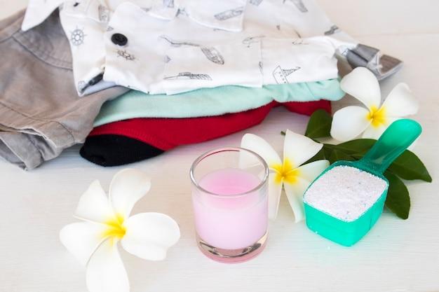 Detergente em pó e solução líquida perto de roupas