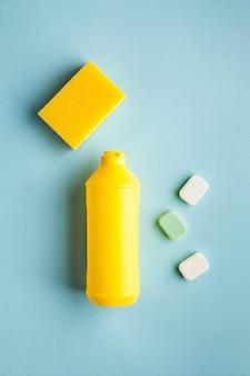 Detergente líquido para lava-louças, comprimidos para lava-louças em uma superfície azul