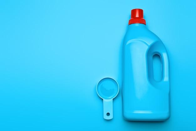 Detergente para roupas e colher na superfície colorida