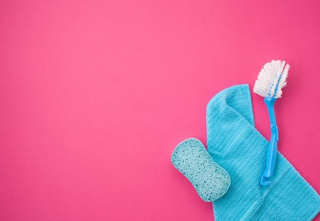 Detergentes e acessórios de limpeza em fundo de cor pastel