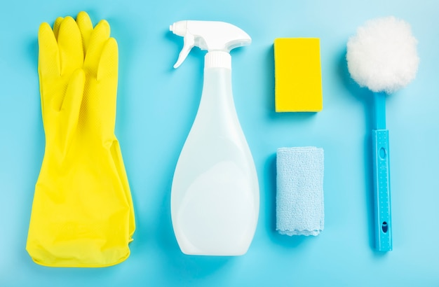 Detergentes e agente de produtos de limpeza, esponjas, guardanapos e luvas de borracha, fundo azul. vista do topo