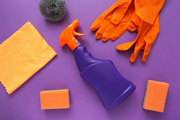 Detergentes e agente de produtos de limpeza, esponjas, guardanapos e luvas de borracha, fundo roxo.