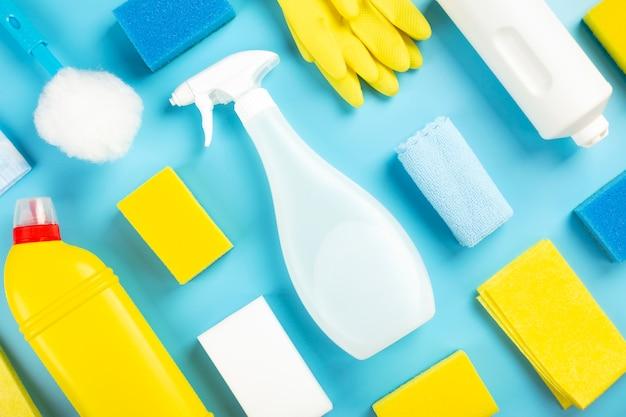 Detergentes e produtos de limpeza, esponjas, guardanapos e luvas de borracha, fundo azul. vista do topo