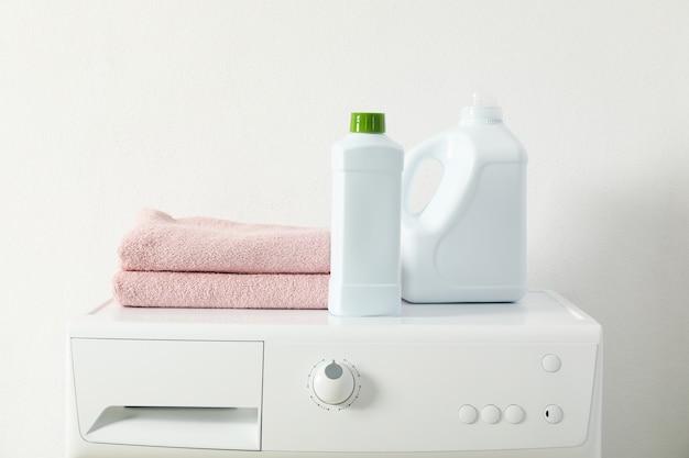 Detergentes e toalhas na máquina de lavar, espaço para texto