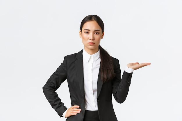 Determinada jovem empresária asiática de aparência séria apresenta seu projeto, mostrando algo na palma da mão, segurando a mão direita no espaço em branco, como apresentar o produto, em pé em um fundo branco de terno preto