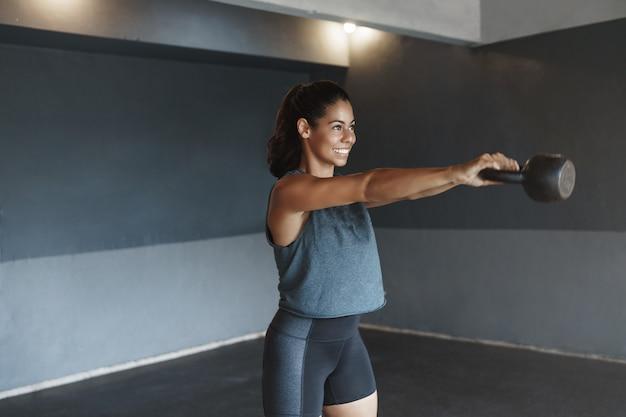 Determinada mulher hispânica forte e suada malhando sozinha na academia com kettlebell