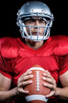 Determinado desportista segurando futebol americano