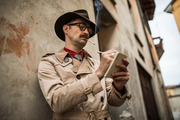 Detetive, escrevendo em um notebook enquanto stadning contra uma parede velha