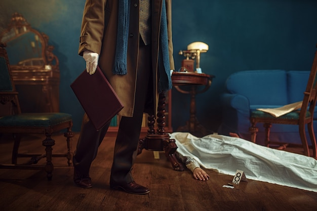 Detetive masculino com casaco segura uma pasta de couro, vítima sob a capa na cena do crime