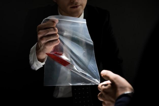 Detetive mostrando uma evidência em investigação criminal