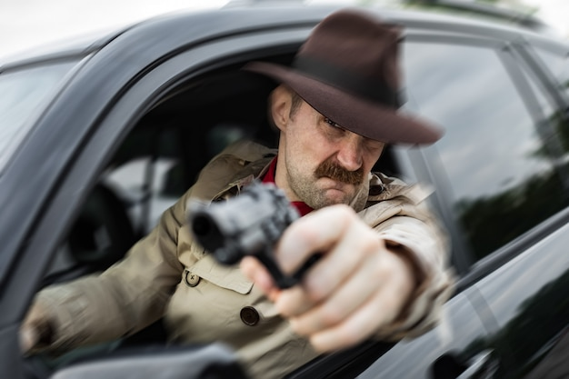 Detetive perseguindo um criminoso de carro e atirando nele com sua arma
