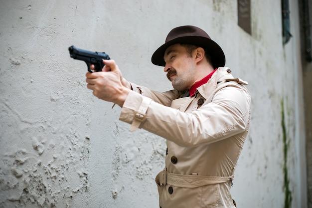 Detetive se escondendo e mirando com a arma