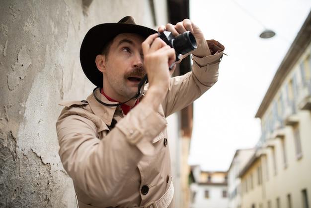 Detetive tirando fotos em uma favela com sua câmera vintage