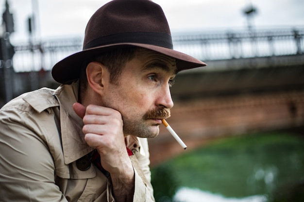 Detetive vintage fumando um cigarro e olhando deprimido