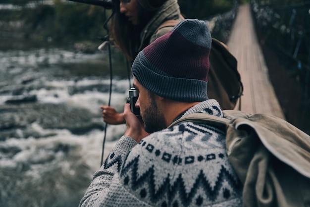 Devemos capturar isso! jovem homem moderno fotografando o rio em pé na ponte pênsil com a namorada