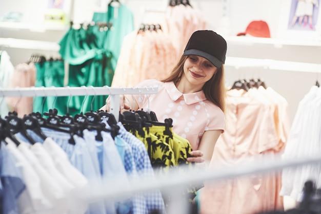 Devemos olhar para novos vestidos. duas lindas meninas estão procurando roupas na loja. bom dia para fazer compras